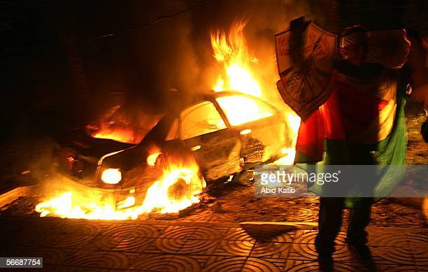 A car burns during a demonstration by Fatah members outside the Palestinian parliament January 27 2006 in Gaza City Gaza Strip Thousands of Fatah...