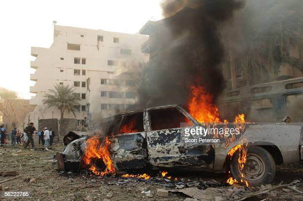 A car burns in the aftermath of a double suicide car bomb attack that struck civilians living near the blast walls that protect the Hamra Hotel...