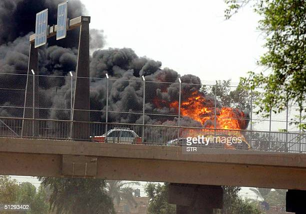 A car burns on a bridge near the road leading the Iraqi capital to Baghdad International Airport 12 September 2004 US troop set this vehicle on fire...