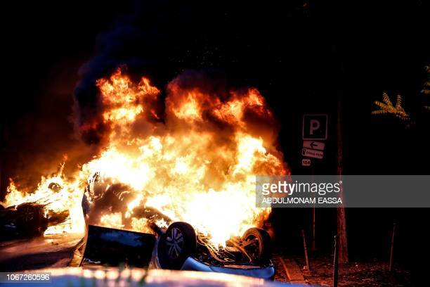 TOPSHOT A car burns on the sideline of a demonstration by Yellow vests against rising oil prices and living costs on December 1 2018 in Paris