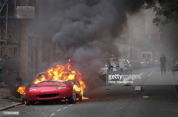 A car burns outside a Carhartt store in Hackney on August 8 2011 in London England Pockets of rioting and looting continues to take place in various...