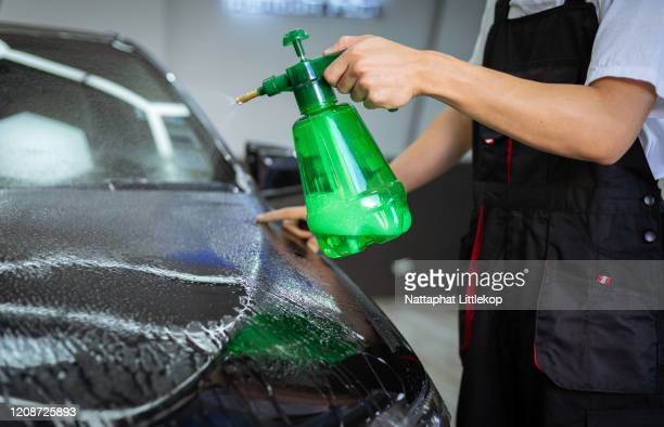 car cleaning auto service : the man sprays water - car detailing concepts - car wash brush stock pictures, royalty-free photos & images