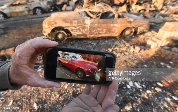 Car collector Gary Dower displays a photo showing his 1973 MGB Roadster before it burned at his home in Santa Rosa California on October 20 2017...