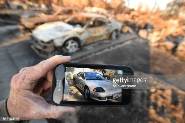 Car collector Gary Dower holds up a photo showing his 1992 Dodge Stealth before it burned at his home in Santa Rosa California on October 20 2017...