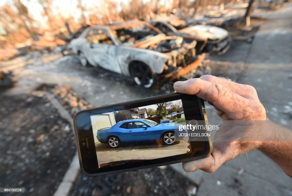TOPSHOT - Car collector Gary Dower holds up a photo showing his 2010 Dodge Challenger Limited Edition SRT8 before it burned at his home in Santa Rosa, California on October 20, 2017. Residents are being allowed to return to their burned homes on October 20 to grieve and search through remains. Around 5,700 homes and businesses have been destroyed by the fires, the deadliest in California's history. /