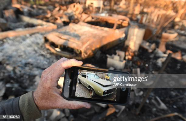 Car collector Gary Dower holds up a photo showing his classic Camero before it burned at his home in Santa Rosa California on October 20 2017...
