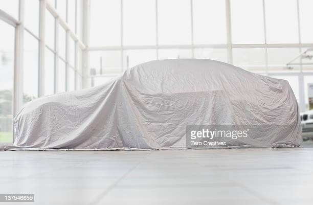 car covered in cloth in garage - showroom stock pictures, royalty-free photos & images