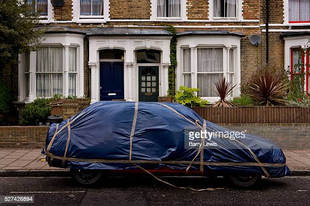 Car covered in protective wrapping fixed by parcel tape to hide it or to keep it clean covered against bad weather while it is kept out on the road
