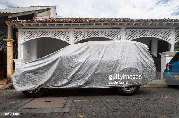 Car covered with a tarpaulin