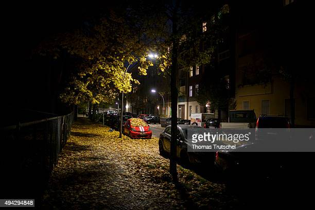 A car covered with autumn leaves parks under a street lamp in a street at night in Berlin Neukoelln on October 25 2015 in Berlin Germany