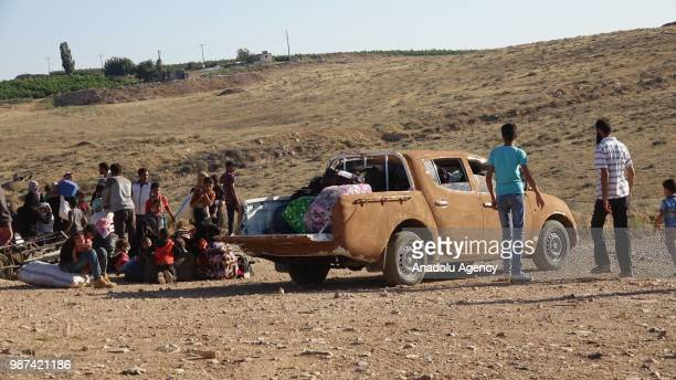A car covered with mud is seen as Syrians wait at the border areas near Jordan after they fled from the ongoing military operations by Bashar alAssad...