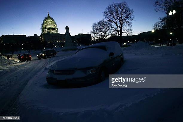 A car covered with snow is seen in front of the US Capitol on January 24 2016 in Washington DC The blizzard that has brought massive snowfall and a...