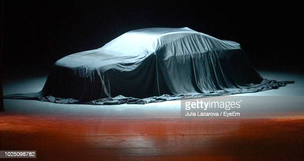 car covered with textile against black background - covering stock pictures, royalty-free photos & images