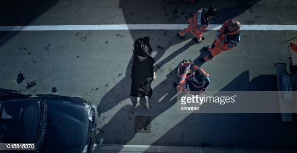 car crash victim covered with black sheet and paramedic team walking away - of dead people in car accidents stock pictures, royalty-free photos & images