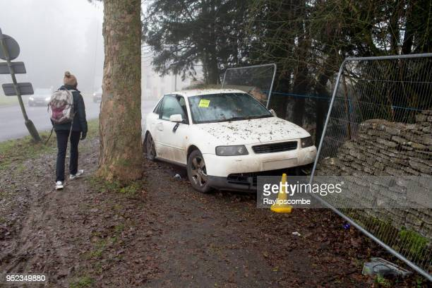 car crashed into a stone wall off a roundabout in cirencester, gloucestershire, england on a foggy winter's morning - car crash wall stock photos and pictures