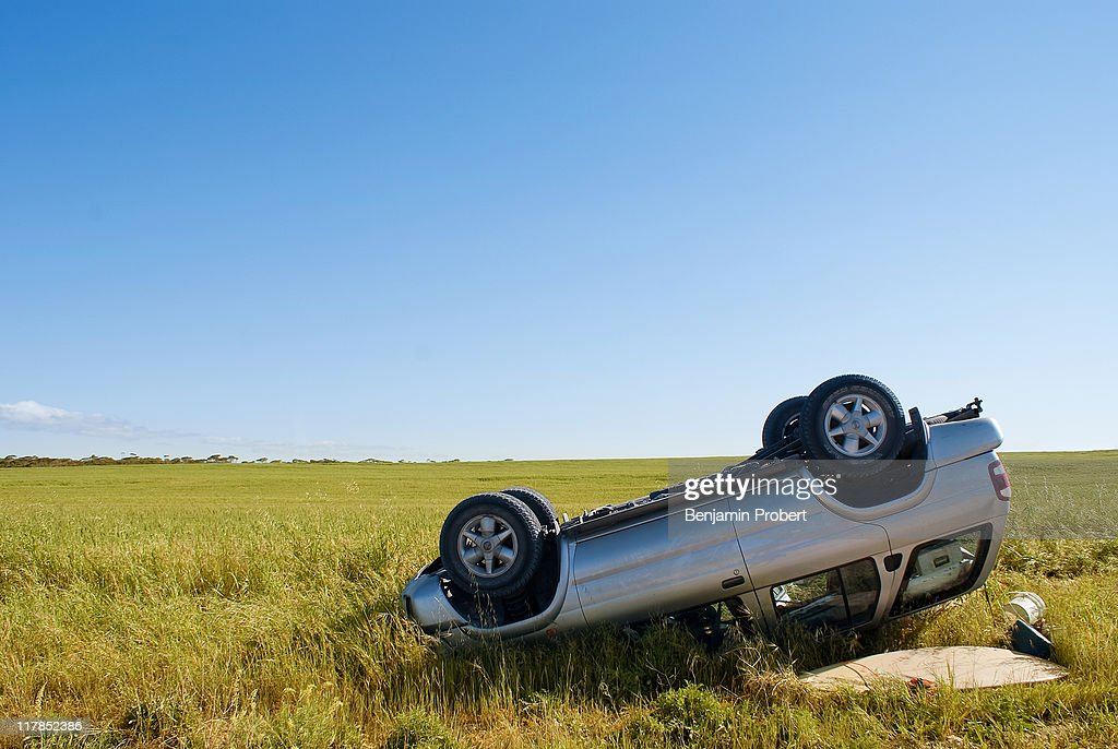 Car crashed on country road with field and sky : Stock Photo
