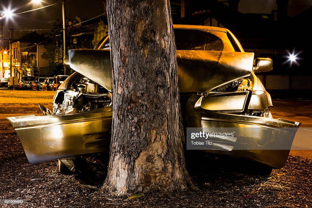 Car crashed on tree trunk at night : Stock Photo