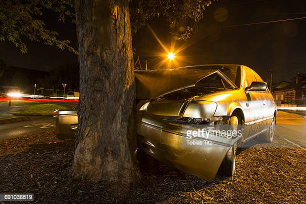 car crashed on tree trunk during night - crash photos stock-fotos und bilder