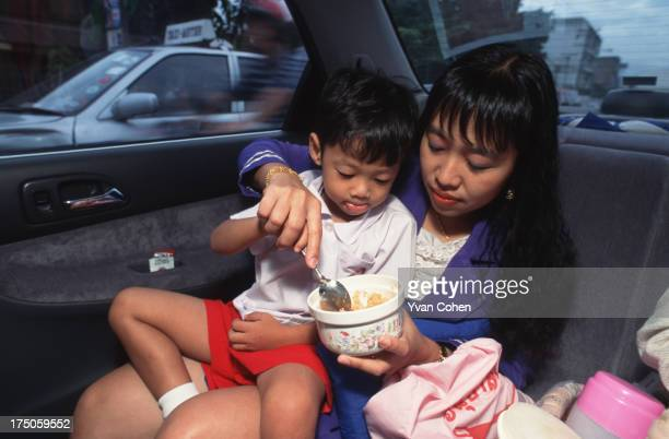 Car culture A mother feeds her son his breakfast on the way to school Huge traffic jams are forcing Bangkokians to spend more and more time in their...