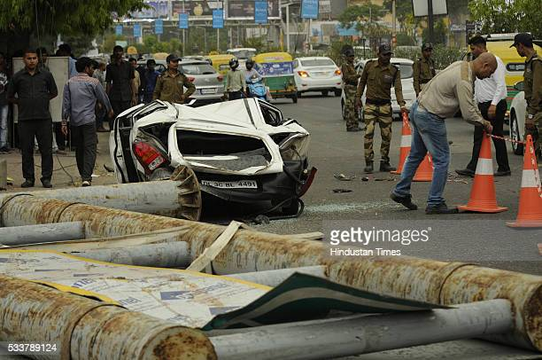 A car damaged and its driver injured as signboard collapsed during a dust storm outside the gate of DLF Mall of India on May 23 2016 in Noida India...