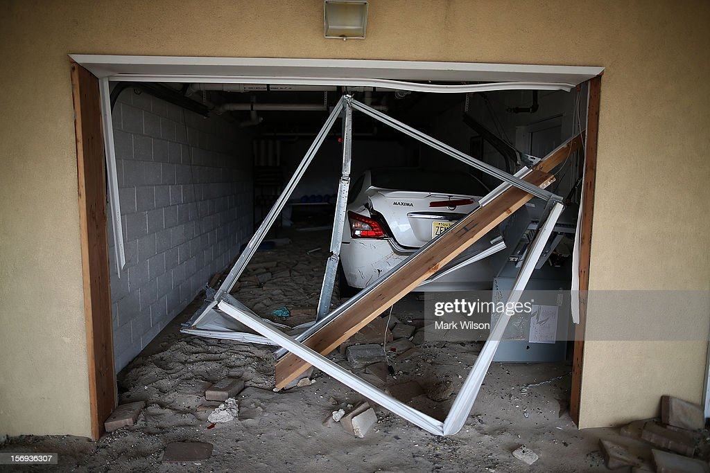 A car damaged by Superstorm Sandy sits in the garage of a beach front home on November 25, 2012 in Seaside Heights, New Jersey. New Jersey Gov. Christie estimated that Superstorm Sandy cost New Jersey $29.4 billion in damage and economic losses.