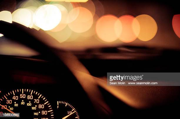 Car dashboard at night with blurred lights