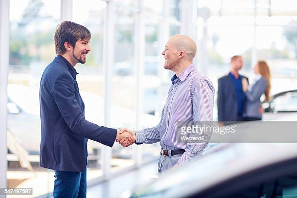Car dealer and client shaking hands