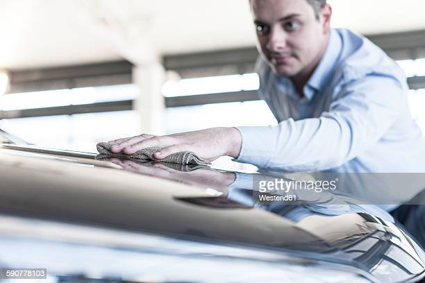 Car dealer cleaning new car