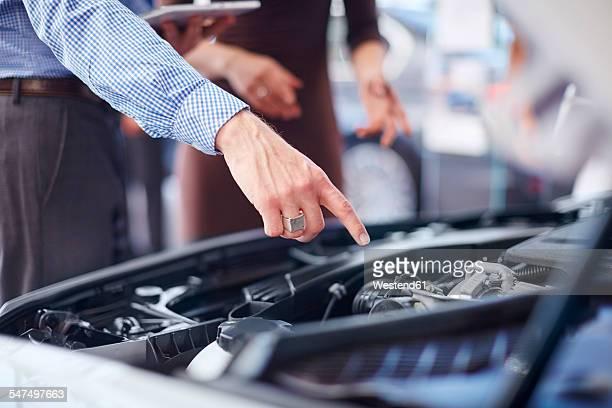Car dealer explaining car engine