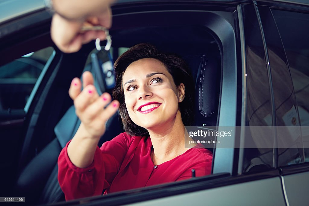 Car dealer gives car keys to the businesswoman : Stock Photo