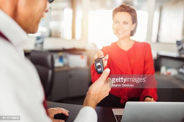 Car dealer giving car keys to the client