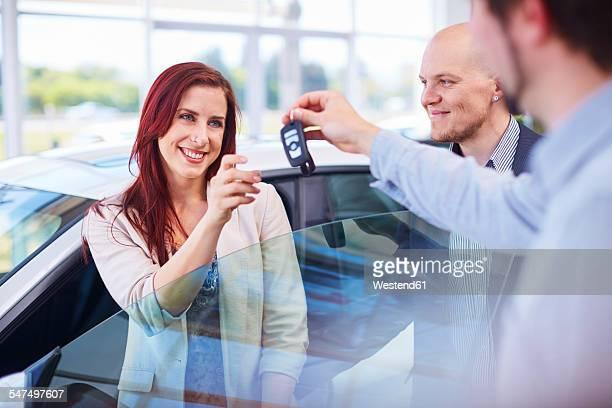 Car dealer giving key to client