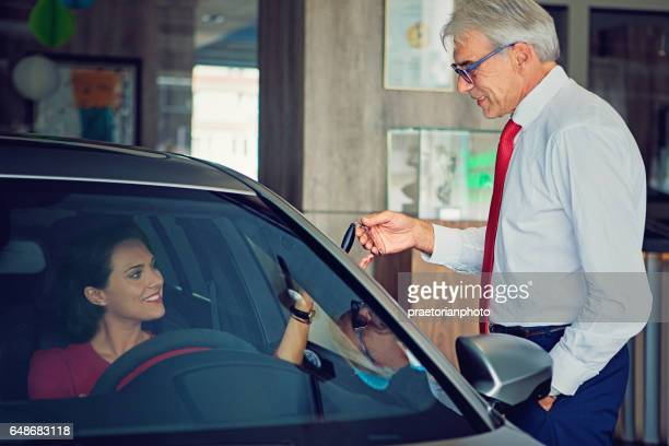 car dealer is giving car keys to a businesswoman - domestic car stock pictures, royalty-free photos & images