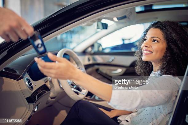car dealer is giving key for a new car to a businesswoman - prestige car stock pictures, royalty-free photos & images