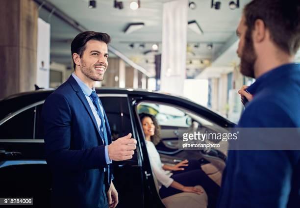 Autohändler präsentiert, paar im Showroom eine