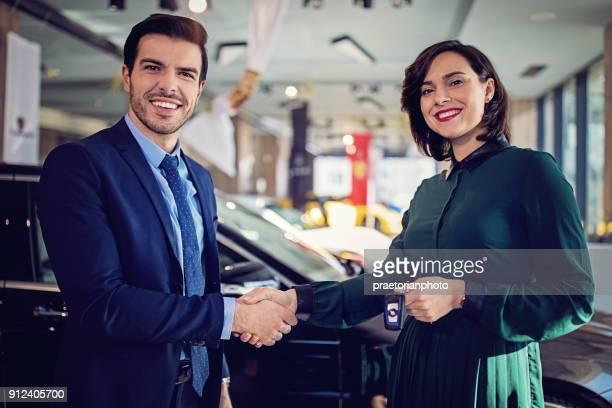 vendedor de carros é apertar a mão com um cliente depois de negócio bem sucedido - acabando - fotografias e filmes do acervo