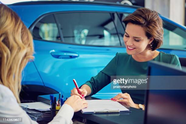 car dealer sales car to the customer and they are signing the contract - lease agreement stock pictures, royalty-free photos & images