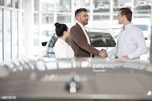 Car dealer shaking hands with man in car dealership