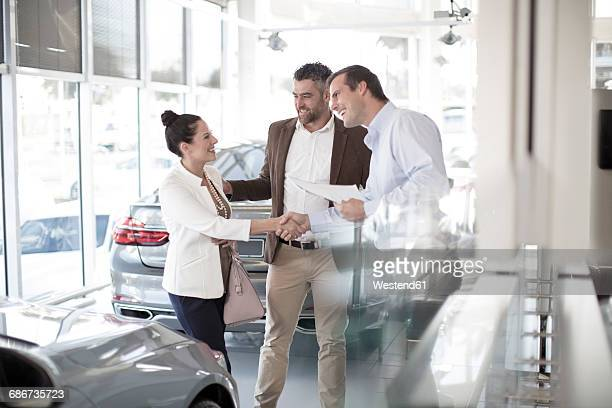 Car dealer shaking hands with woman in car dealership