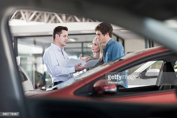 Car dealer showing brochure to young couple in showroom