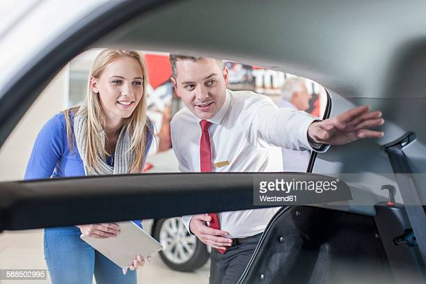 Car dealer showing new car to woman in showroom
