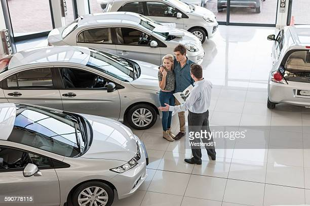 car dealer showing new car to young couple in showroom - car dealership stock pictures, royalty-free photos & images
