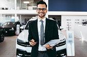 Car dealer standing and posing in showroom