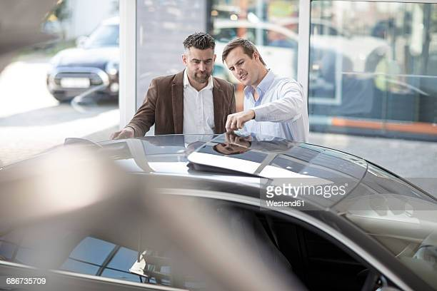 Car dealer talking to client at car dealership