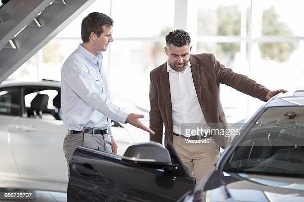 Car dealer talking to client in showroom