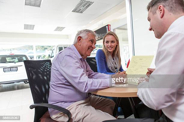 Car dealer talking to clients at table