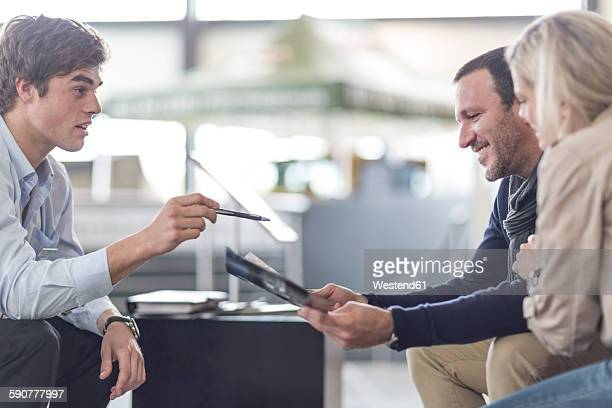 car dealer talking to couple - stock trader stock pictures, royalty-free photos & images