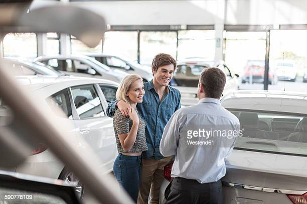 Car dealer talking to young couple in showroom