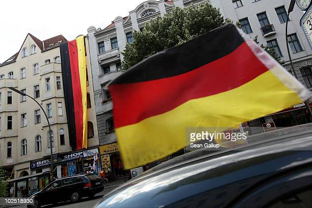 A car decorated with a German flag drives past a fourstorey long German flag hanging over the electronics shop of local Muslim resident Youssef...