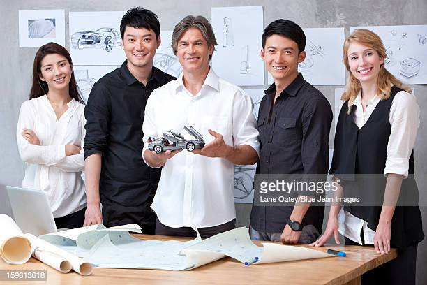 Car designers studying a model car
